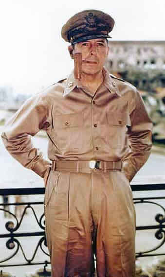 Photographic image of General MacArthur dressed in military khakis with a pipe in his mouth.